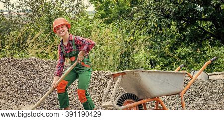Girl With Wheelbarrow Of Rubble. Kid Working On Construction Site. Teen Girl Takes Out Rubble From W