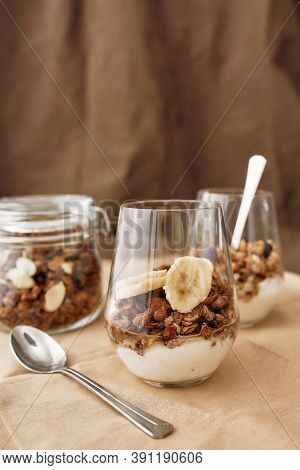 Close Up Of Delicious Layered Dessert In Glass Jar, Homemade Yogurt With Granola And Banana, Granola