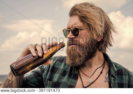 Brutal Caucasian Hipster With Glass Water Bottle. Male Bachelor Lifestyle. Bearded Man Drink Beer. H