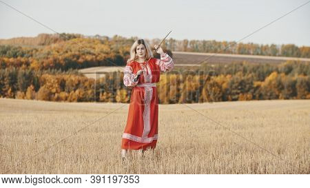 Militant Woman In National Red Clothes Stands In A Field With A Sword