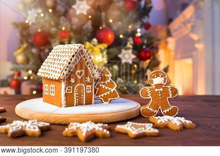 Homemade Gingerbread House On The Background Of A Decorated Christmas Tree And Unfocused Lights With
