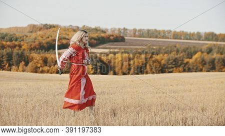 Militant Woman In Red Clothes Stands In A Field With A Sword