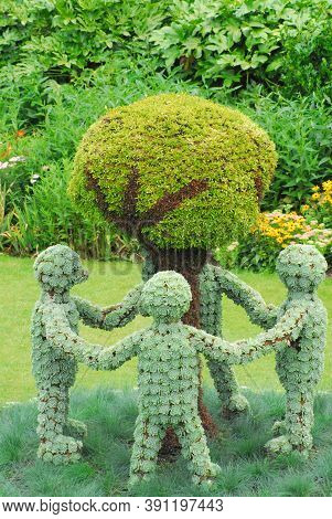 A Charming Group Of Topiary Figures Depicting Four Children Holding Hands And Encircling A Tree.  Sh