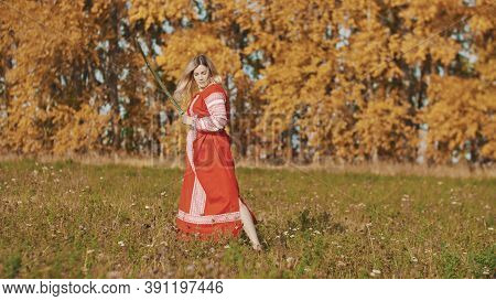 Militant Woman Posing On Autumn Field With Sword