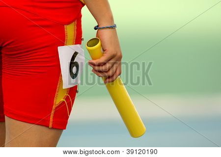 Athlete with a baton waiting for a relay event