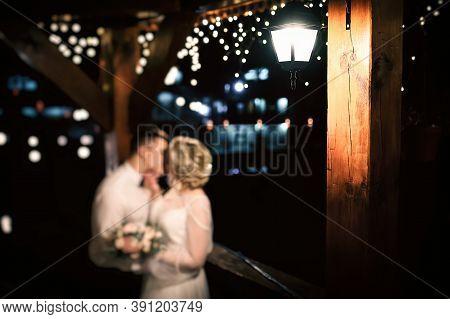 A Couple In Love In Out Of Focus Kissing At Night Under A Streetlight. Wedding Concept.