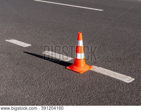 New Orange Traffic Cone With White Stripes On The Road Without Cars. Road Works. Traffic Safety