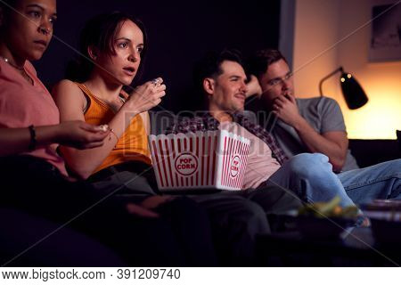 Group Of Friends Eating Popcorn Sitting On Sofa At Home Watching Horror Movie Together