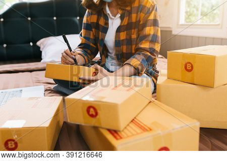 Close Up Online Shopping Young Women Start Small Business In A Cardboard Box At Work. The Seller Pre