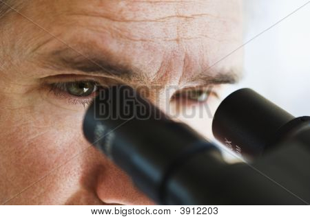 Close Up Of Man\'s Eyes Looking Through Microscope