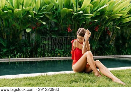 Enjoying Suntan And Vacation. Colorful Portrait Of Pretty Young Woman In Red Swimsuit Near Swimming
