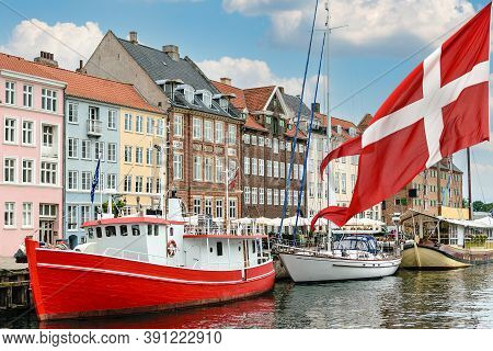 Nyhavn A 17th Century Harbour In Copenhagen With Typical Colorful Houses And Boats With National Fla