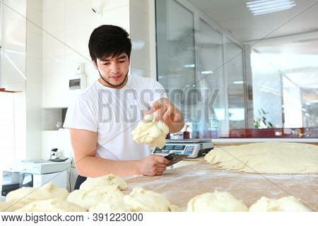 A Young Baker Puts A Portion Of Dough On The Table. The Process Of Making Tortillas. Hands And Dough