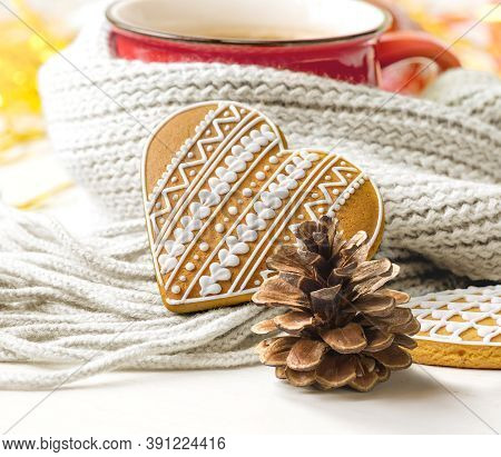 Gingerbread Cookies In The Shape Of Heart, Pine Cone And Red Mug With Hot Drink Wrapped In Scarf. Co