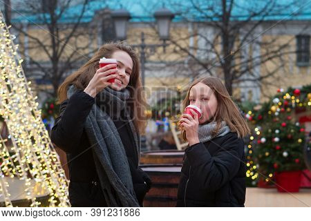 Two Adorable Sisters Drinking Coffee On Traditional Christmas Fair. Girls Spends Time Together At Th