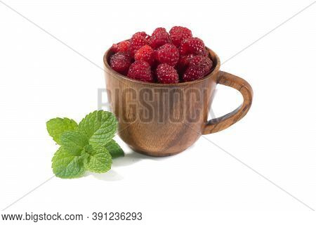 Raspberries In A Wooden Cup On A White Background. Mug Of Delicious Raspberries Isolated On White.