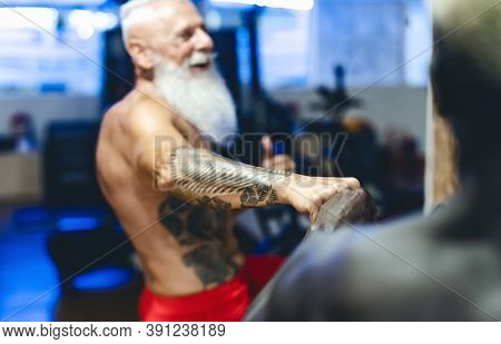 Athletes With Different Age And Race Doing Bike Exercises In Gym - Fit People Training On Cycling Ma