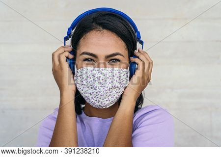 Young Woman Wearing Face Mask Listening To Music With Wireless Headphones - Latin Girl Using Protect