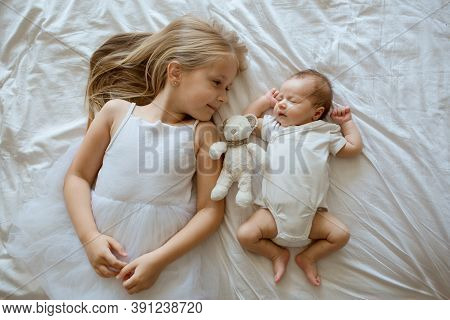 Little Sister And Her Newborn Brother. Toddler Kid Meeting New Sibling. Cute Girl And New Born Baby