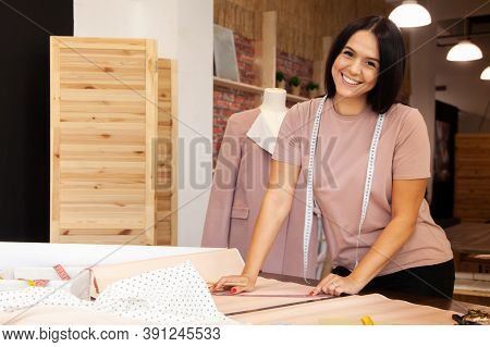 Female Tailor Unfolding Tracing Paper For Sewing Patterns In Atelier
