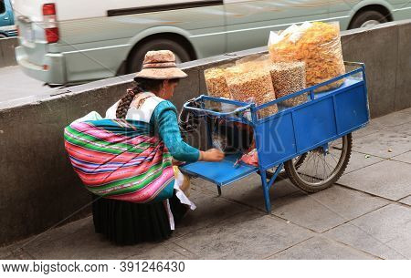 Street Vendor With Her Cart Filled With Delectable Snacks, The Sidewalk In Downtown La Paz, Bolivia,