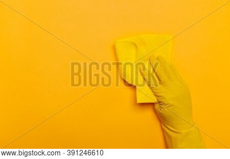 A Hand In Yellow Gloves Holds A Yellow Rag On A Yellow Background. Place For Text.