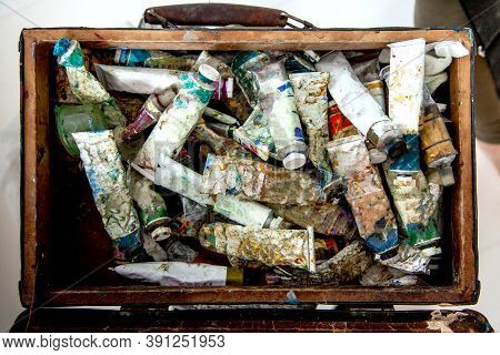 Painter Hands Picking Oil Paint Tube From Collection Of Neglected And Messy Artist Oil Paint Tubes