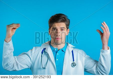 Handsome Bored Doctor Man In Medical Coat Showing Bla-bla-bla Gesture With Hands And Rolling Eyes Is