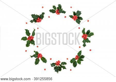 Winter, Christmas & New Year natural holly berry wreath with loose red berries on white background. Flat lay top view, copy space. Design element.