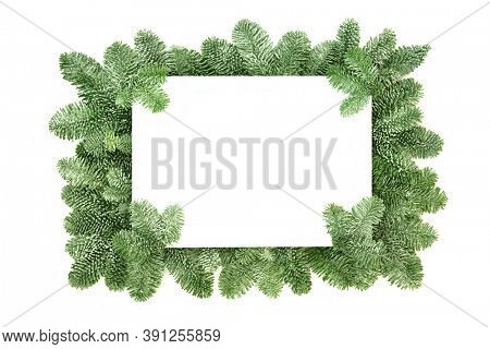 Winter solstice & natural greenery border with snow covered fir on white background with copy space. Festive element for Christmas & New Year season. Top view, flat lay.