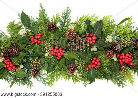 Christmas & winter greenery with holly, ivy, mistletoe, cedar cypress leaves & pine cones on white background. Xmas & New Year decoration for the festive holiday season. Flat lay, top view.