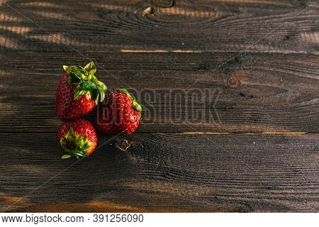 Three Fresh Juicy Strawberries Lie On An Old Table From A Dark Wood Background.
