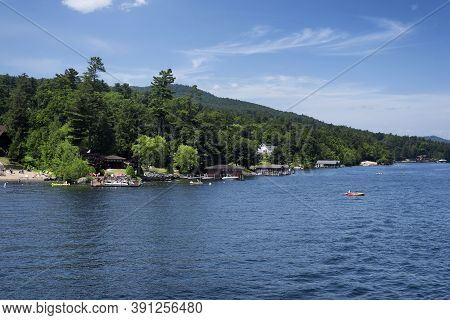 Lake George, New York.  July 19, 2019. Tourists Active On The Shores Of Lake George On A Sunny Blue