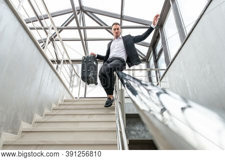 Happy Businessman Wearing Formal Suit Sliding On Stairs Railing In Modern Business Building. Hurry A