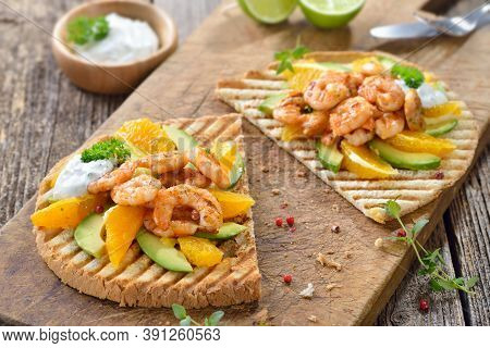 Crunchy Large Toast With Grilled Prawns On Avocado And Orange Slices With Dill Lime Sauce