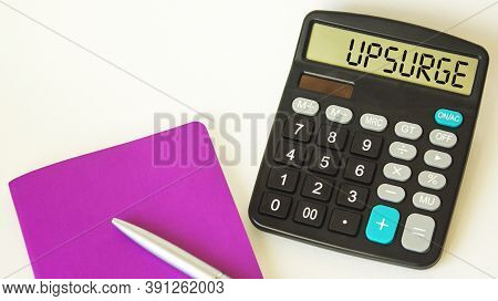 The Word Upsurge , On A Calculator, Next To A Notepad With A Pen On A White Background