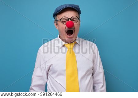 Senior Cheerful Man With Red Nose Yawning Being Tired.