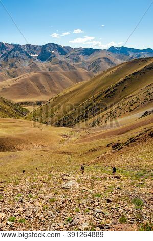 Group Of Trekkers Descending Rocky Pass With Mountain Top Wiews In High Mountains. Young Men And Wom