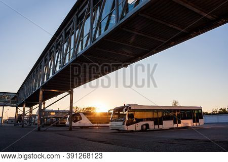 Shuttle Buses At The Parking Lot Of The Airport Near The Jetway In The Rays Of The Setting Sun