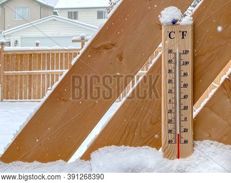 A Thermometer On A Snow Fall With A Cold Temperature.