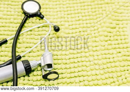 Stethoscope And Ear Watcher From A Veterinary Center On Top Of A Green Blanket.
