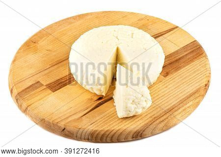 Round Soft Cheese With A Cut Triangular Piece On A Wooden Cutting Board. Cheese On A Cutting Board I