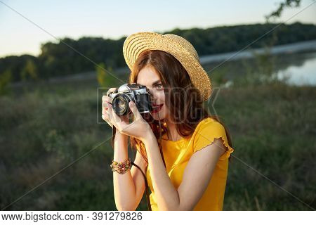 Woman Photographer Looking Into The Camera Lens Wearing A Hat Outdoors Takes A Picture