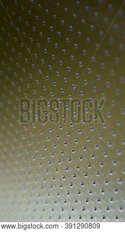 Industrial Mobile Phone Wallpaper In Olive Or Bronze Color. Perforated Metal Surface With Many Holes
