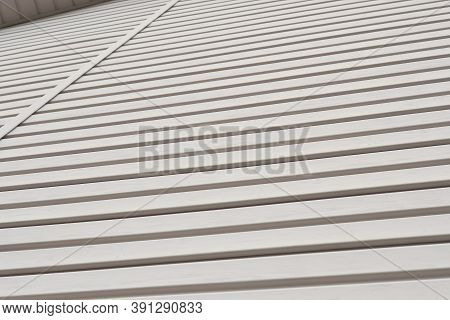 Striped Plastic Siding Surface And Piece Of Cornice. Light Beige Brown Background Or Wallpaper. Back