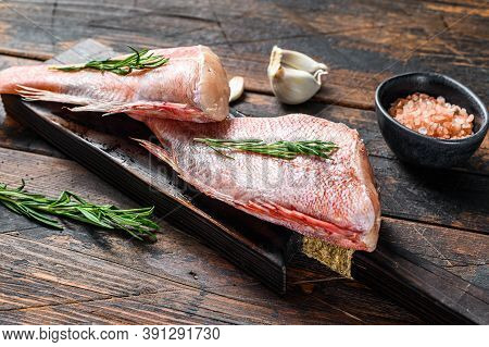 Whole Raw Red Snapper Fish On A Cutting Board. Dark Wooden Background. Top View. Copy Space