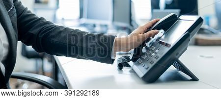 Close-up Of A Female Employees Hand On A Landline Phone. Woman Picks Up A Push-button Telephone At T