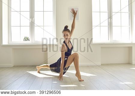 Graceful Flexible Attractive Female Gymnast Trains And Dances In A Large Bright Dance Hall.