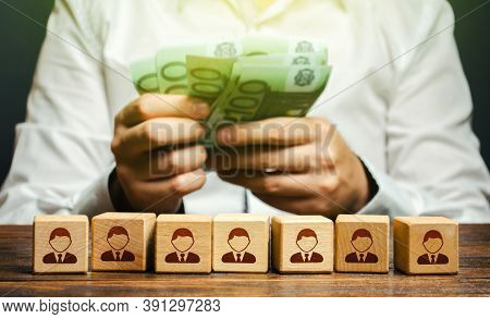A Man Is Counting Euro Money In His Hands Over Blocks With Symbols Of Employees. Wage Fund. Accounti