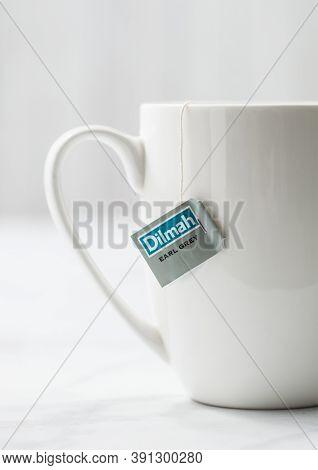 London, Uk - October 21, 2020: Dilmah Earl Grey Tea In White Ceramic Cup On Light Background. Macro